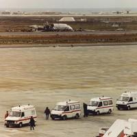 Ziekenwagens wachten op een toestel dat gewonden naar Nederland brengt. Het ramptoestel ligt nog langs de baan.