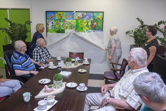 Kleurrijke beestenboel in hal verpleeghuis; patiënten maken groepsschilderij