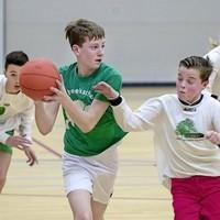Basketbal in Sporthal Oost: Jan Campertschool tegen Bosbeekschool (groen shirt).
