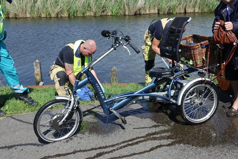 Omstanders halen vrouw op driewieler uit water in Wijdewormer