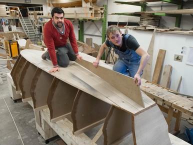 Het leggen van de kiel. Nick van Stralen (l) en Timo Kruk (r) bovenop het omgekeerde scheepje.