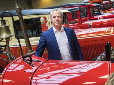 Veilingmeester Koen Samson poseert bij een Ford brandweerwagen, cadeautje van Heineken.