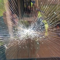 De schade aan het raam in de toegangsdeur.