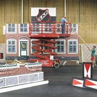Vrijwilligers Leo Huiberts, Adrie Duynhoven en Frans van Stein (vla.) bouwen in de Zwaluwhal Hotel Spaander weer op.