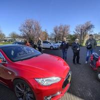 Bezoekers van de informatiedag bekijken een Tesla, de Ferrari onder de elektrische auto's.