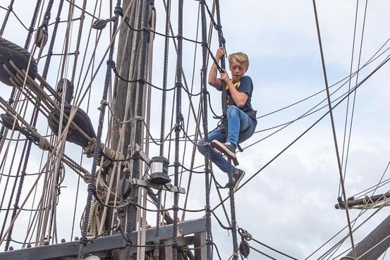 Jongste bemanningslid Jeppe Bösal (12) klimt in het want van zeilschip de Halve Maen