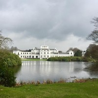 De achterkant van het paleis gezien over de vijver.