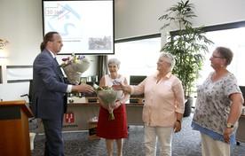 Wethouder Sven Lankreijer geeft bloemen aan de drie leden van de WAC Eemnes.