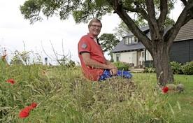 Simon Bakker op een tuinwal bij zijn huis onder de perenboom die zijn overgrootvader ooit geplant heeft.