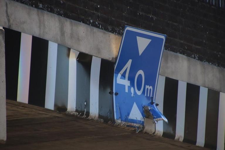 Vrachtwagen met haakarm omhoog tegen brug onder A44, inzittende gewond