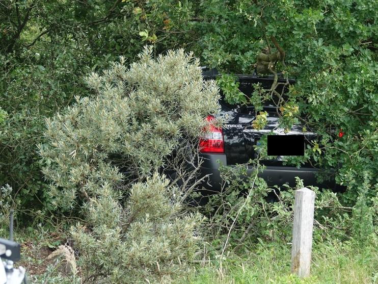 Auto belandt via hek in struiken, twee personen naar ziekenhuis