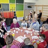 Ouderen laten zich de pannenkoeken op De Drietand goed smaken terwijl ze kletsen met de kinderen.
