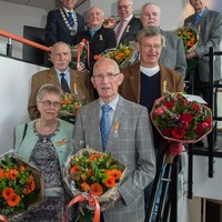 Uit handen van burgemeester Don Bijl ontvingen Klaas Post, Fred Rijswijk, Gerrie Cramer (achterste rij), Lex Kriger, Martien Roelofs (midden) en het echtpaar Hanny en Jules Somers een Koninklijke Onderscheiding.