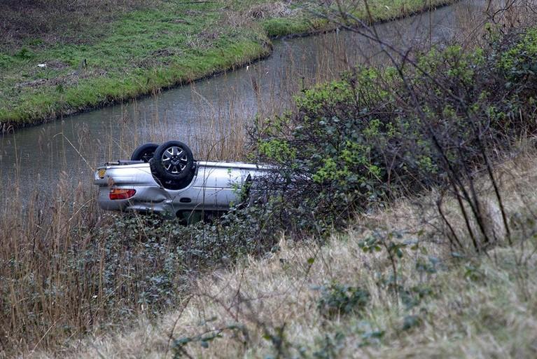 Automobilist rijdt van talud in Haarlem, voertuig belandt in water