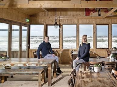 Tanja Bredewout met zoon Kevin in haar strandpaviljoen te Camperduin. Het strand voor hen is weg.