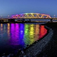 De brug over de IJssel bij Westervoort is aangelicht in regenboogkleuren. De buurgemeente van Arnhem doet dit uit protest tegen de mishandeling van twee homoseksuele mannen in die stad.