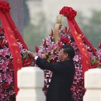 De Chinese president Xi Jinping schikt lelies tijdens een nationale feestdag in Beijing.