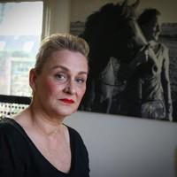 Moeder Tinne Kroone, met op de achtergrond een foto van haar dochter.