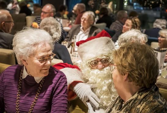 Genieten van het gezelschap en van het kerstdiner voor ouderen
