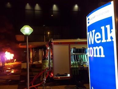 Brandweer blust de auto bij het TMG-pand.