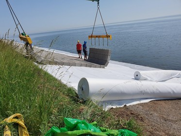 Dijk om marinehaven versterkt met betonmatten