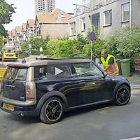 De verkeersregelaar moet steun zoeken op de Mini-motorkap.