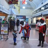 Pegida Nederland-aanhangers delen, verkleed als Zwarte Piet, pepernoten uit in winkelcentrum Streekhof.