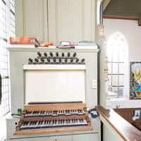 Sybren Rozendal, voorzitter van de Lutherse Kerk Alkmaar, bekijkt de schade aan het eeuwenoude orgel.