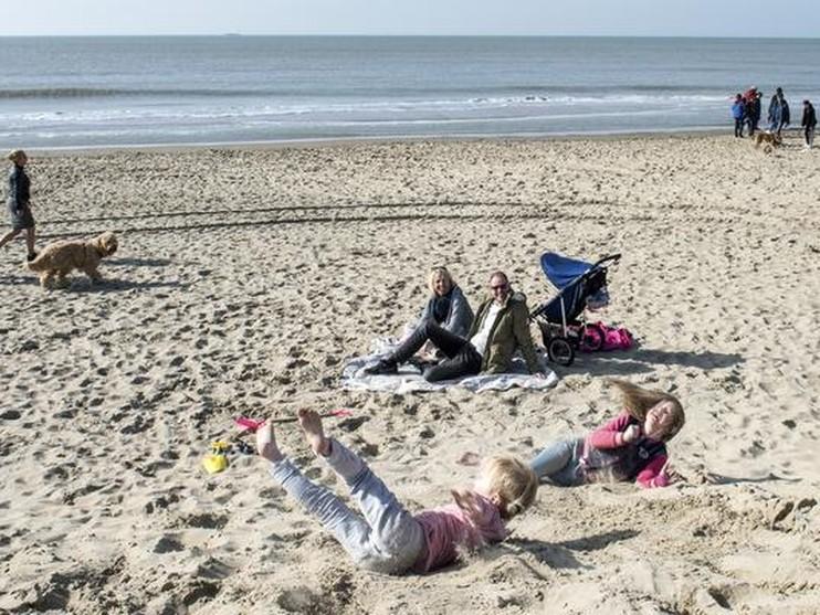 Nicky en Roos rollen over het zand naar beneden.