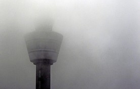 De verkeerstoren van Schiphol gehuld in dichte mist.