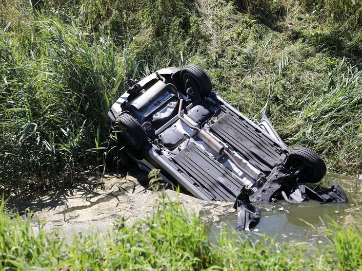Auto over de kop in sloot Abbenes, bestuurder nagenoeg ongedeerd