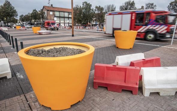Oranje bloempotten brengen kleur en duidelijkheid op kaal parkeerplein in IJmuiden