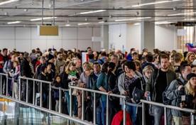 Eind april: reizigers wachten in rijen voor de bagagecontrole op luchthaven Schiphol.