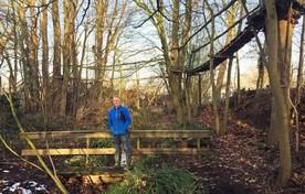 Franke van der Laan op een brug boven de beek in de Heimanshof. in de bomen het 'labyrint''.