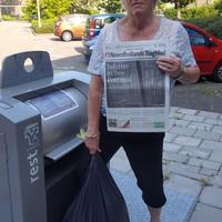 Mevrouw Dekker met de krant van maandag jl als bewijs dat de container weer kapot was.