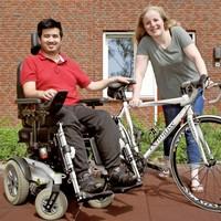 ALS-patiënt Michel de Wit met zijn vriendin Anna Brouwer en zijn racefiets waarop zij nu in zijn plaats fietst.