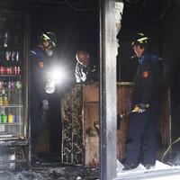 Deskundigen van de politie en de brandweer doen onderzoek in de door brand verwoeste pizzeria.