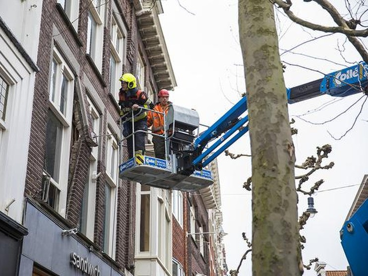Boomsnoeiers trekken gevel uit winkelpand in centrum Haarlem